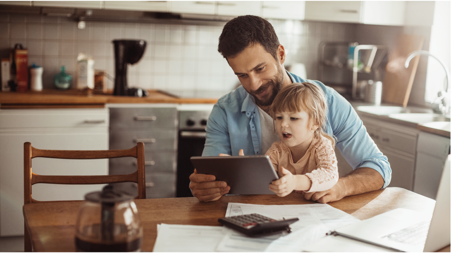 Dad on tablet and kitchen table with young daughter